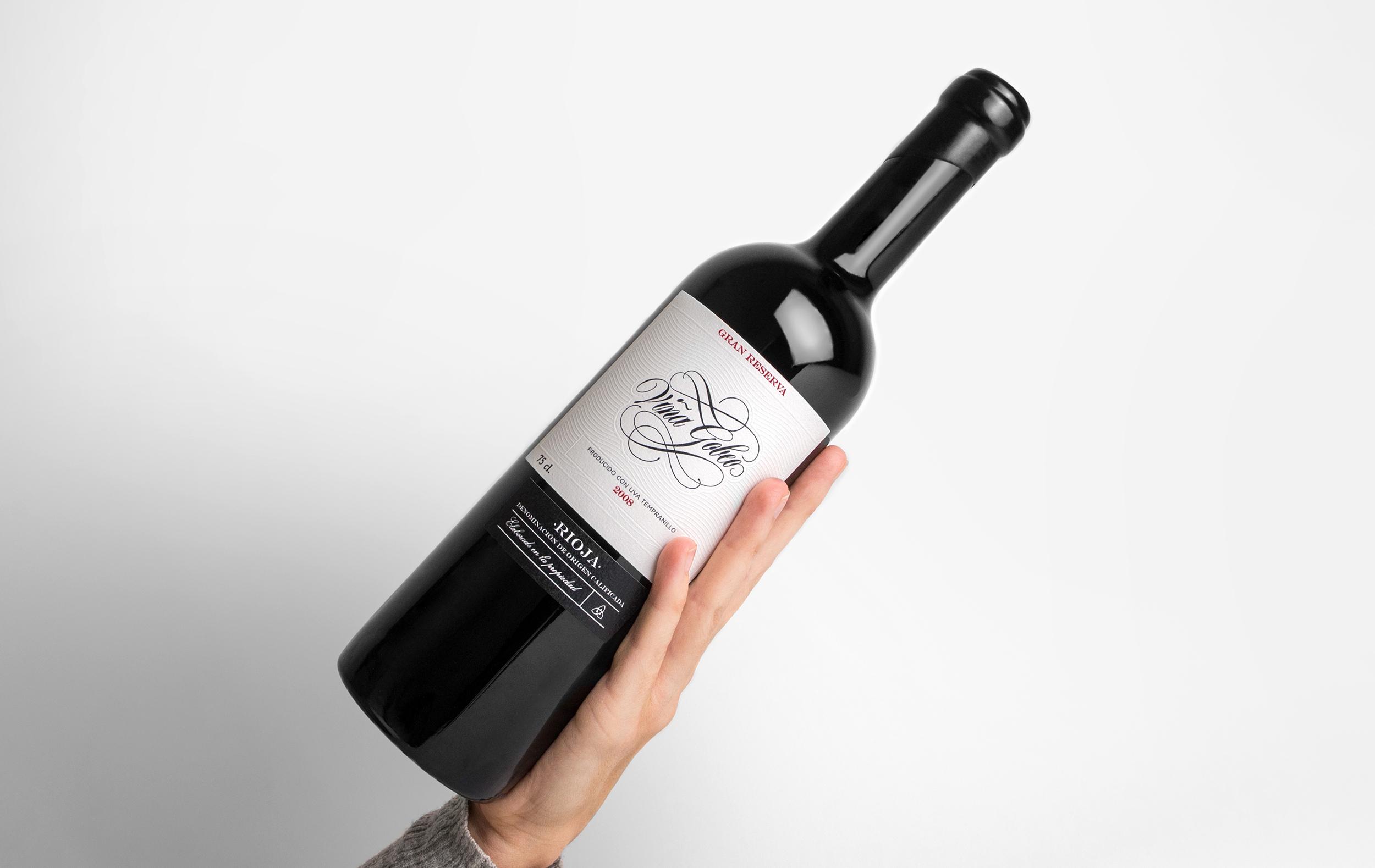 Diseño de etiqueta de vino y fotografía del vino Gran Reserva Viña Gobeo sosteniendo con mano